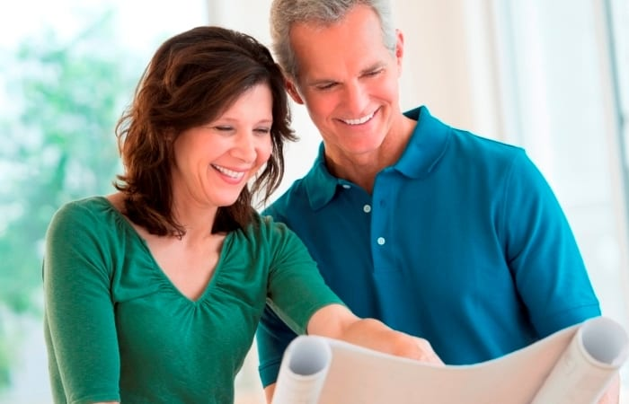 Woman Showing Blueprint To Husband In Renovated House